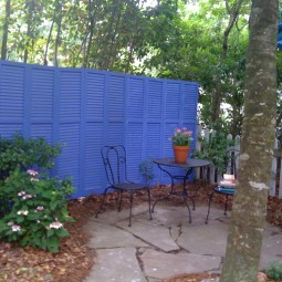 Privacy fence made of assortd old shutters.jpg